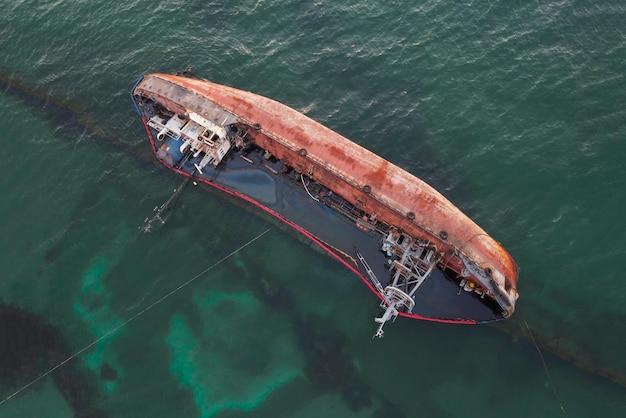 Um navio afundado, um navio-tanque afundado perto da praia, um navio naufragado na água.