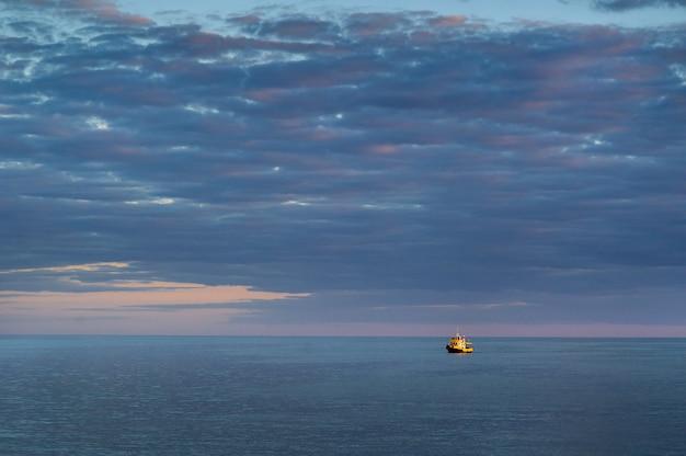 Um navio amarelo no mar báltico aberto. pôr do sol nas nuvens. letão,