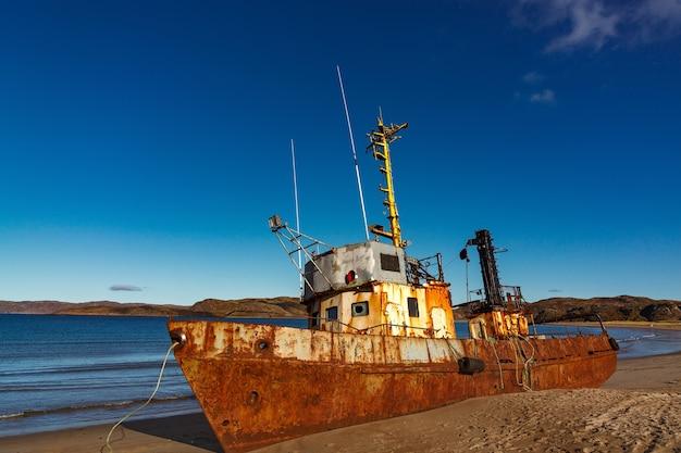 Um navio naufragado em uma praia na maré baixa na baía de teriberskaya. extremo norte, mar de barents, na rússia.