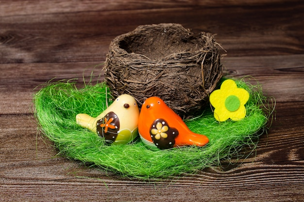 Um ninho de pássaro real e dois pássaros em uma mesa de madeira.