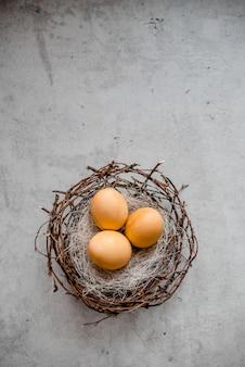 Um ninho e vários ovos com varas de salgueiro. fundo de pedra cinza abstrata, conceito de páscoa feliz