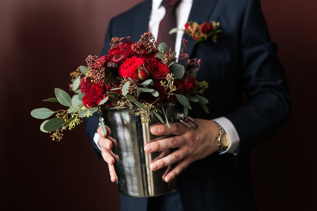 Um noivo em uma camisa branca e elegante terno formal detém e estende um buquê de casamento lindamente desenhado de diferentes flores e folhas verdes, close-up.