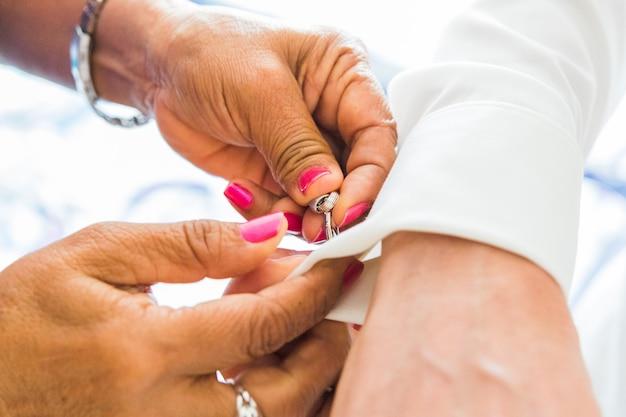 Um noivo que põe sobre botões de punho como adquire vestido em seu dia do casamento. terno do noivo