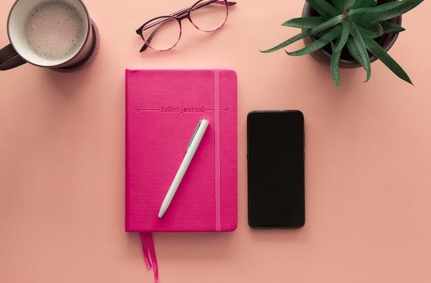 Um notebook com lápis e celular
