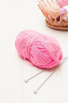 Um novelo de linha rosa e agulhas de tricô na mesa