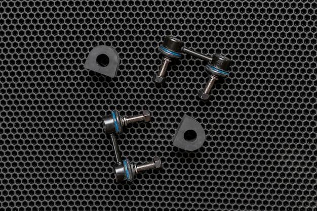 Um novo carro peças sobressalentes, braços detalhes da suspensão isolados em fundo escuro plano lay