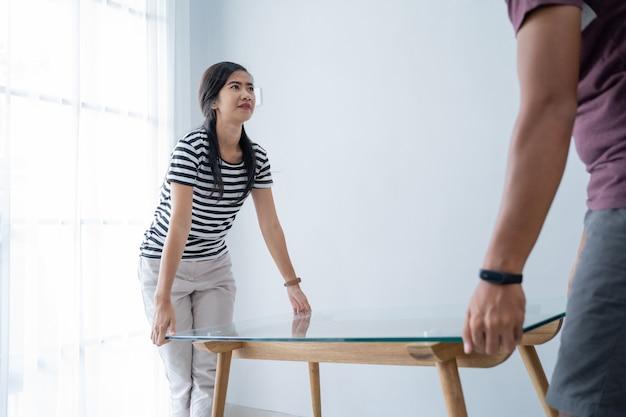Um novo casal traz uma mesa para mover móveis de interior