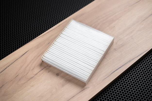 Um novo filtro de ar de carro quadrado branco para cabana plana em fundo escuro