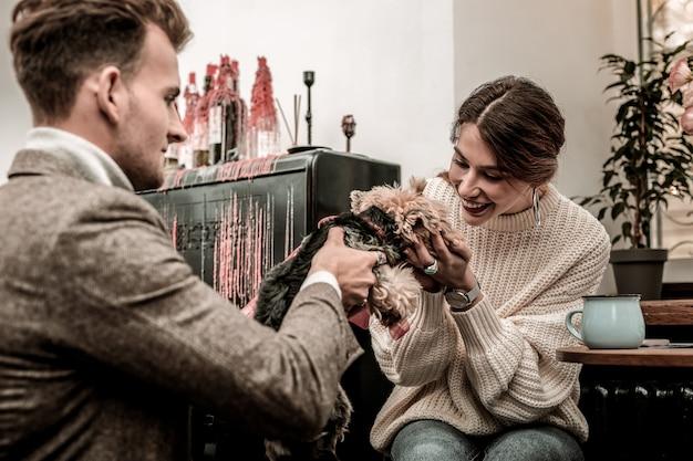 Um novo membro da família. uma mulher e um homem segurando um cachorrinho feliz