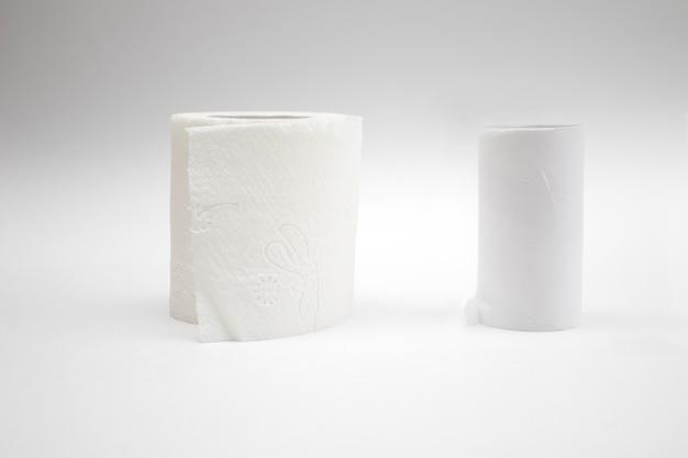 Um novo rolo de papel higiênico e rolos de papel higiênico vazio no fundo branco.