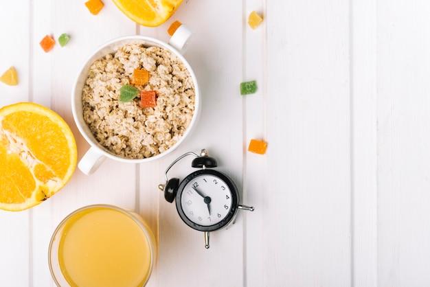Um óculos laranja e mingau de aveia com despertador na mesa branca