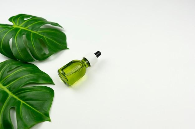 Um óleo verde cbd e folhas verdes de monstera repousam sobre uma mesa branca