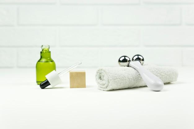 Um óleo verde cbd, rolo facial e toalha de algodão branco repousam sobre uma mesa branca
