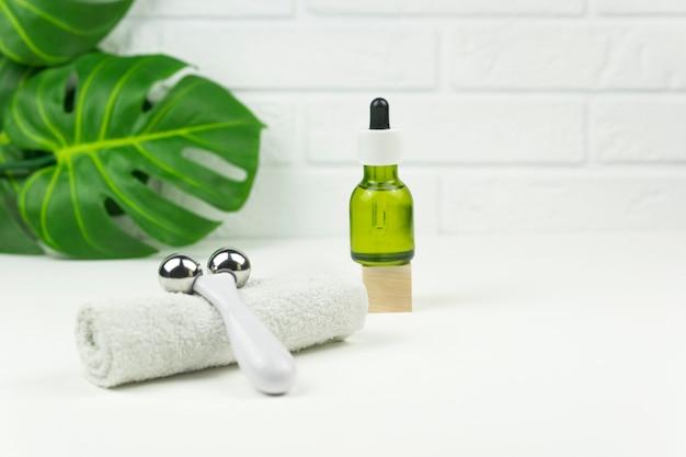 Um óleo verde cbd, rolo facial, toalha de algodão branco e folhas verdes de monstera repousam sobre uma mesa branca