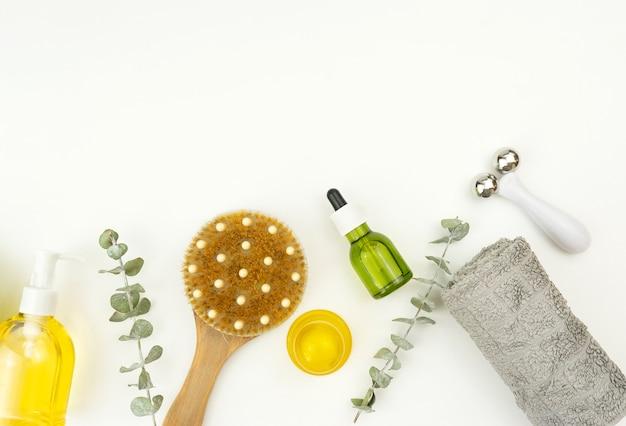 Um óleo verde cbd, um rolo facial e uma escova para massagem a seco repousam sobre uma mesa branca em um banheiro