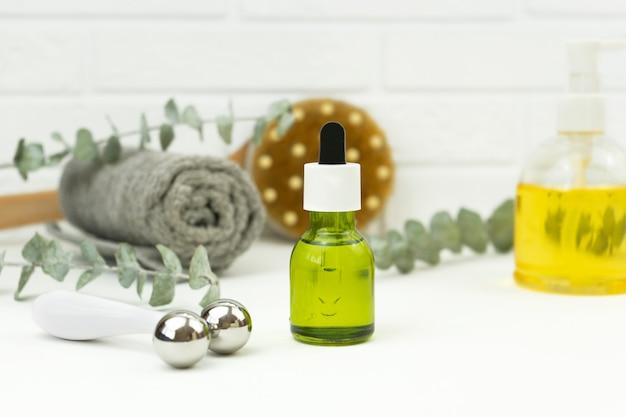 Um óleo verde cbd, um rolo para massagem facial, uma toalha de algodão branco e folhas verdes de monstera ficam em uma mesa branca em um banheiro