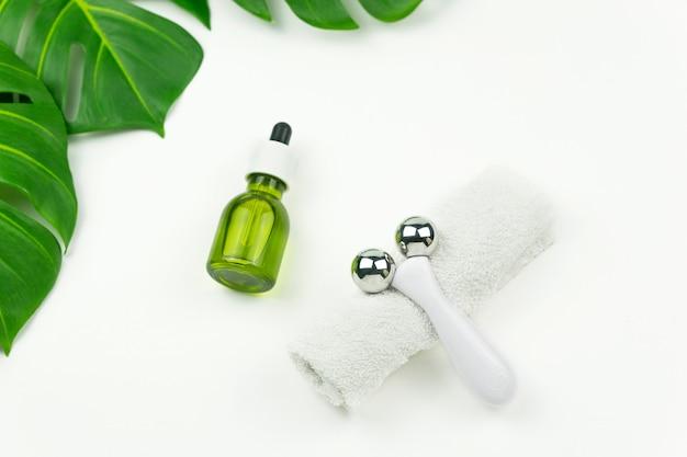 Um óleo verde cbd, um rolo para massagem facial, uma toalha de algodão branco e folhas verdes de monstera repousam sobre uma mesa branca em um banheiro