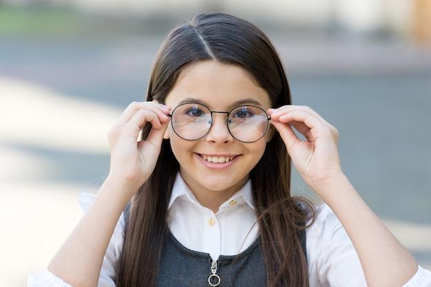 Um olhar intelectual. criança feliz olha através de óculos ao ar livre. exame de visão na escola. teste ocular. óculos corretivos. óculos de prescrição. protetor ocular. salão de óptica. educação primária.