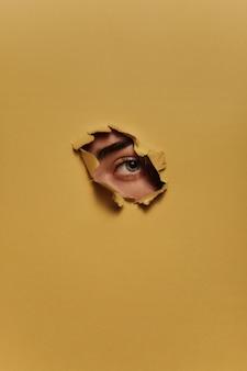 Um olho azul humano está espreitando através de um buraco de papelão rasgado amarelo