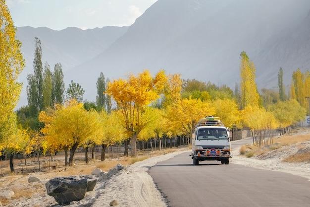 Um ônibus que corre na estrada pavimentada ao longo das árvores coloridas no outono contra montanhas.