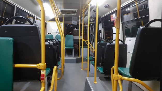 Um ônibus vazio é equipado com corrimãos para segurá-lo por dentro. transporte público urbano e suburbano moderno de passageiros na cidade. assentos de passageiros.