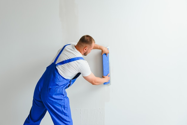 Um operário de macacão usa uma espátula para cobrir a parede com cimento