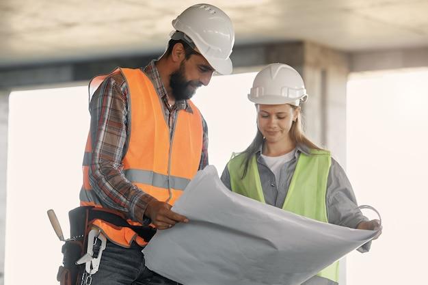 Um operário e um engenheiro fazem uma inspeção. operário de fábrica e mulher de negócios na linha de produção discutindo o plano de trabalho