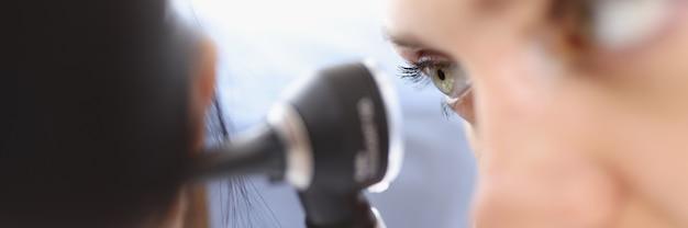 Um otorrinolaringologista examina o close up da orelha do paciente