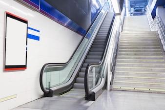 Um outdoor branco vazio na parede perto da escada rolante e escada