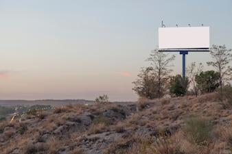 Um outdoor de publicidade vazio na montanha contra o céu