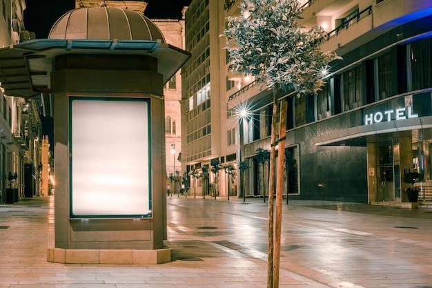 Um outdoor iluminado perto da rua