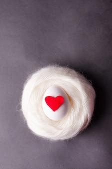Um ovo branco com um coração vermelho encontra-se em um ninho morno aconchegante