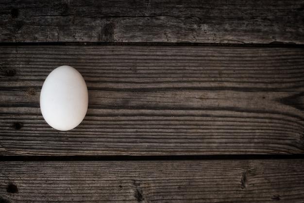 Um ovo branco encontra-se na velha madeira escura