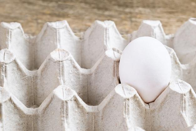Um ovo branco no pacote em fundo de madeira.