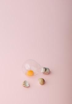 Um ovo cru em uma lâmpada e cascas ao lado dele easter minimal concept fundo rosa