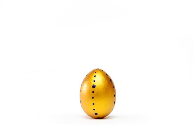Um ovo da páscoa na moda colorido dourado no branco.