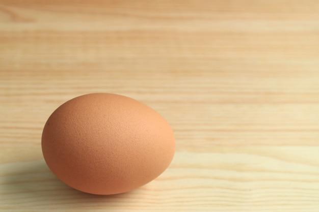 Um ovo de galinha cru fresco isolado na mesa de madeira