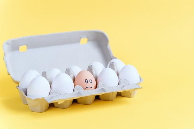 Um ovo de laranja com cara triste desenhada entre ovos brancos em uma bandeja de papelão. diferente de outro.