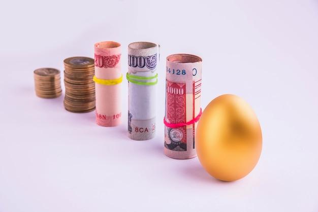 Um ovo de ouro colocado verticalmente em uma linha com rolos de dinheiro indiano ou papel-moeda amarrados com elástico, isolado sobre fundo branco