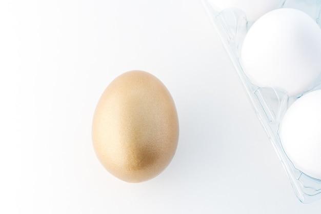 Um ovo dourado e ovos brancos em branco