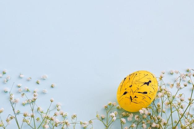 Um ovo é amarelo com manchas pretas e flores em um fundo azul claro com uma cópia do espaço. páscoa. minimalismo. fundo festivo. cartão postal. quadro