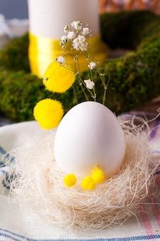 Um ovo em um ninho com elementos de produtos de floricultura - elementos da mesa festiva da páscoa, uma opção para servir