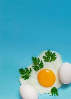 Um ovo frito com salsa em um azul ao lado de dois ovos crus.