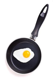 Um ovo frito na frigideira de teflon sem óleo isolado no branco