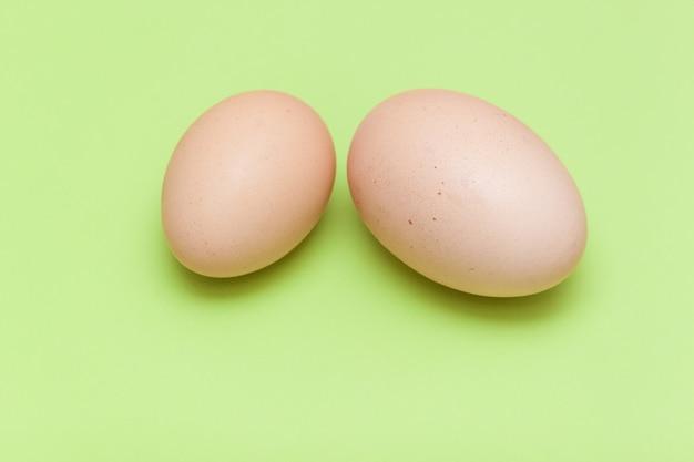 Um ovo grande e um ovo pequeno na luz - fundo verde.