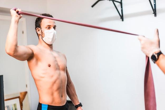 Um paciente com uma máscara ajudou a fazer exercícios de braço com o fisioterapeuta. fisioterapia com medidas de proteção para a pandemia de coronavírus, covid-19. osteopatia, quiromassagem terapêutica