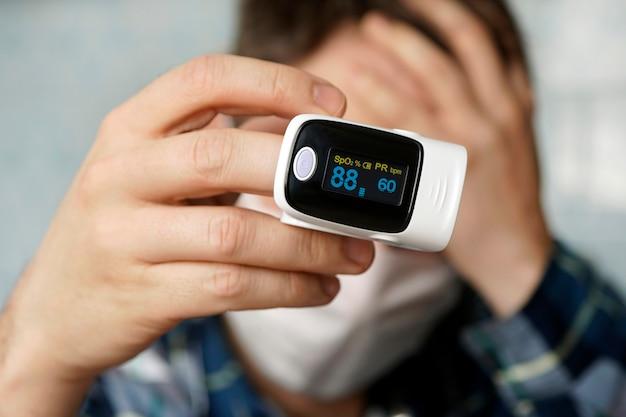 Um paciente com uma máscara médica mede a saturação do sangue com um oxímetro de pulso eletrônico em seu dedo .. oxímetro de pulso usado para medir a taxa de pulso e os níveis de oxigênio. baixa saturação do sangue.