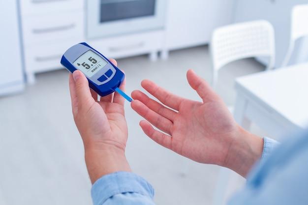 Um paciente diabético mede a glicose no sangue com um medidor de glicose em casa. ter diabetes e controlar o nível sanguíneo de glicose