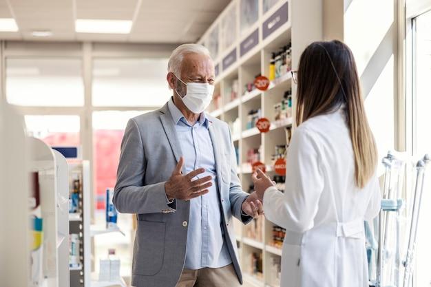 Um paciente em uma farmácia. um homem mais velho conversa com uma farmacêutica e explica algo com as mãos.