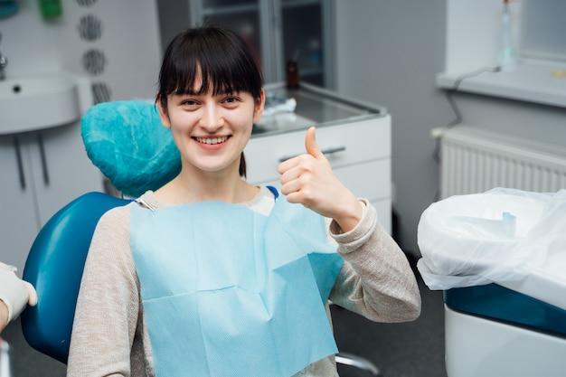 Um paciente fêmea que espera felizmente pelo tratamento em um estúdio dental.